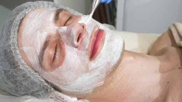 Thumbnail for Relaxed Happy Handsome Man Enjoying Facial Masks at Spa Center