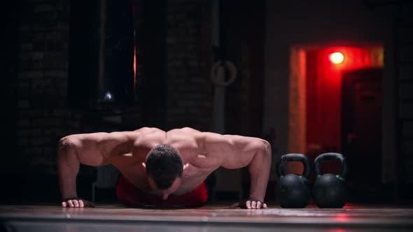 Harter Mann im Fitnessstudio macht Übungen - Push Ups