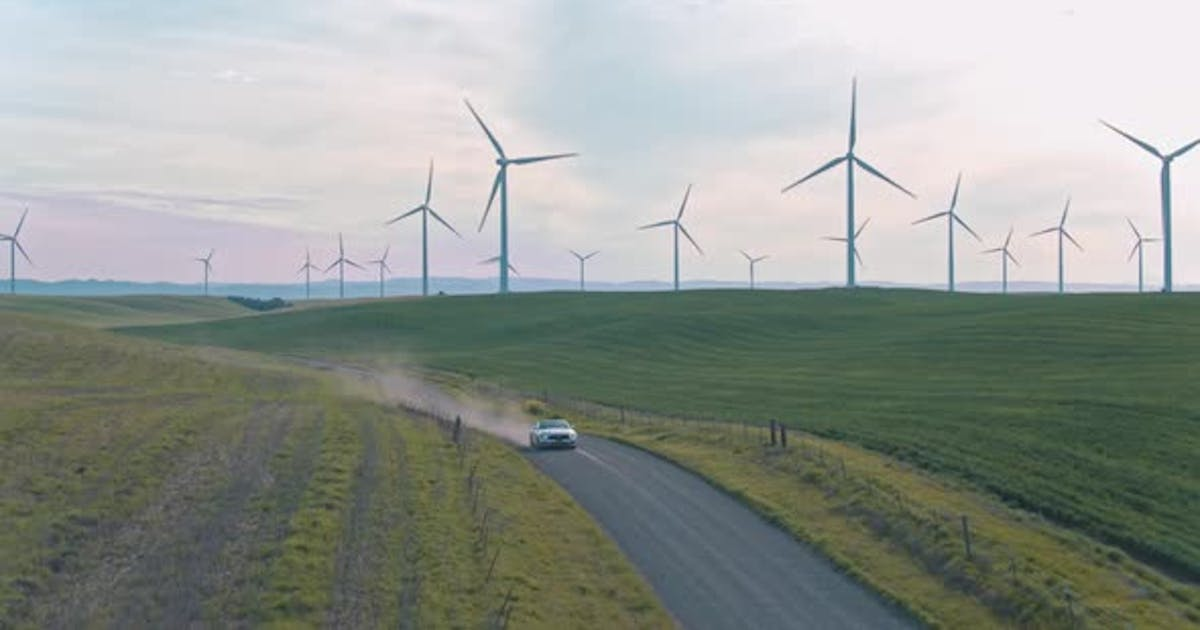 Car Driving On The Dirt Road Among Windmills