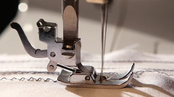 Cover Image for Sewing Machine Sews a Zigzag Stitch on White Fabric. Slow Motion