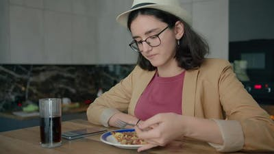 A Girl in a Hat Eating and Browsing a Mobile App