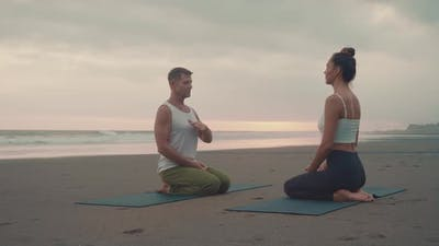 People Practicing Breathing Techniques on Beach