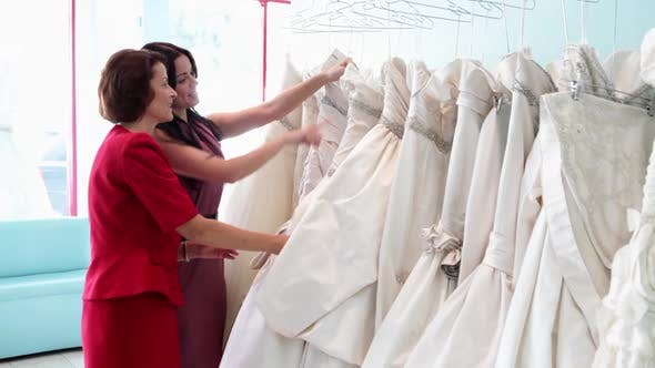 Thumbnail for Mother and daughter looking at wedding dresses
