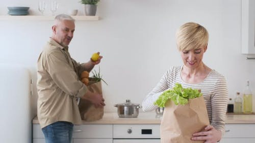Happy Couple Unpacking Bags After Grocery Shopping Standing In Kitchen