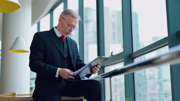 Thumbnail for Portrait of mature man in cafe. Mature businessman sitting at coffee shop with documents