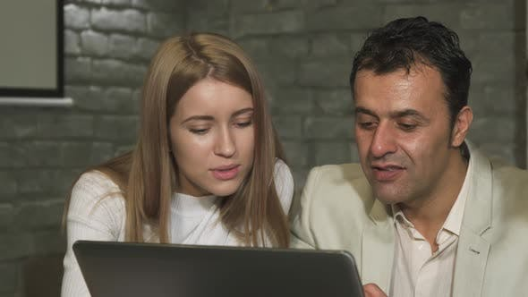 Cover Image for Mature Businessman and His Young Colleague Working on the Laptop