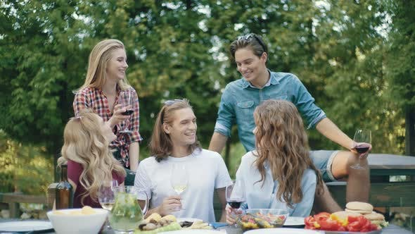 Friends Toasting With Drinks At Dinner Party Outdoors