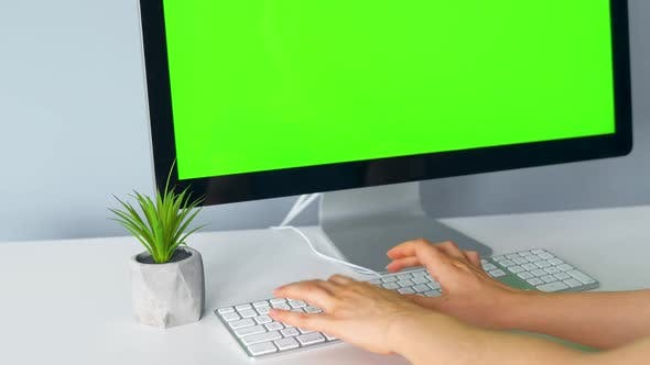 Woman Typing on a Computer Keyboard, Monitor with a Green Screen. Chroma Key. Copy Space.