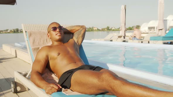 Thumbnail for Handsome African Athletic Man Resting Near the Swimming Pool at the Beach
