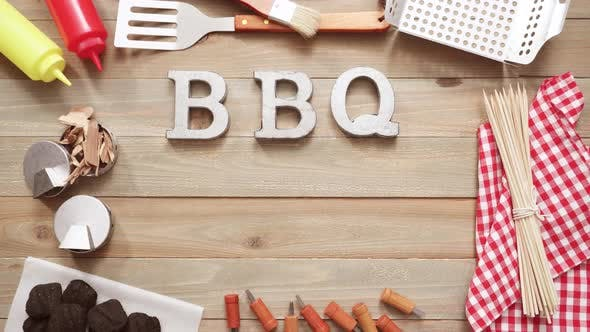Metal BBQ sign with grilling tools on wood background.