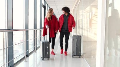 Couple in Red Clothing with Suitcases Going for Flight