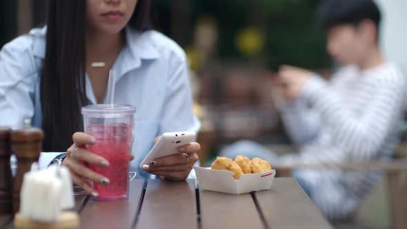 Thumbnail for Woman Typing on Smartphone and Drinking Soda at Lunch