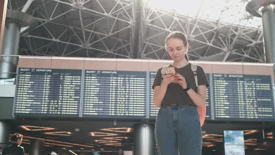 Thumbnail for Young Woman Standing at the Airport Writes a Message
