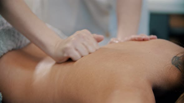 Thumbnail for Massage - with Her Fist the Massage Therapist Is Massaging the Back
