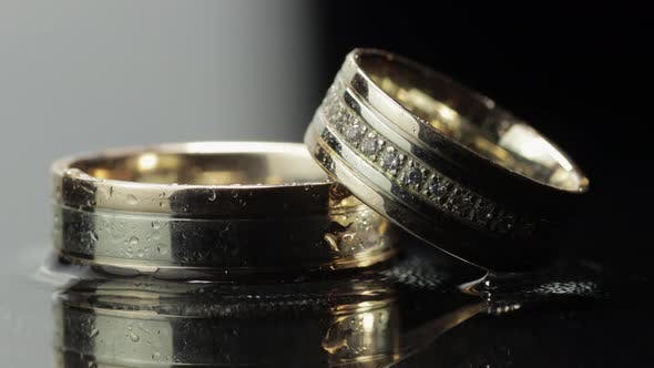 Wedding Rings on Black and White Water Surface Shining with Light