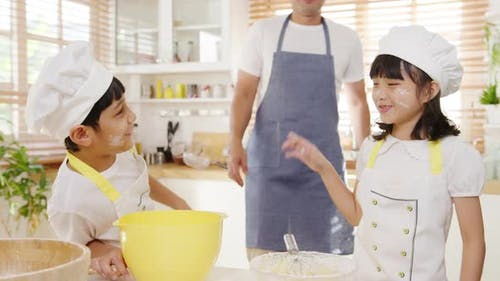 Young Asian family have fun play and laugh while cook cake for breakfast meal in kitchen.