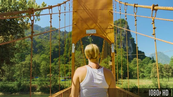 Thumbnail for Woman Walking on Wood Suspension Bridge Walkway in the Mountains of Vang Vieng, Laos