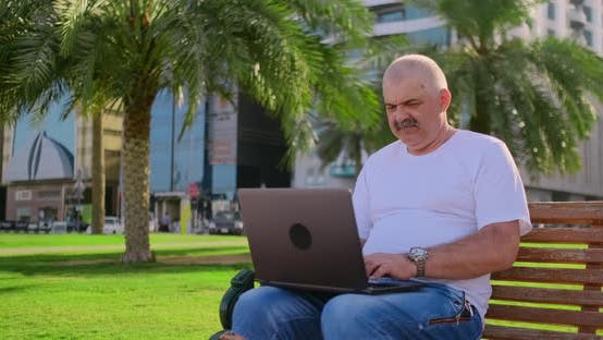 Thumbnail for Senior Man Sitting in Park with Laptop in Summer and Chatting