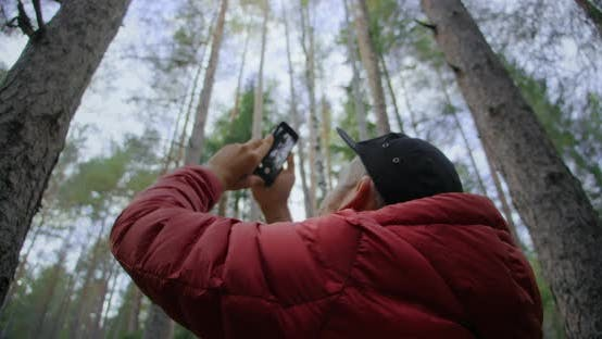 Urban Nomad Hipster Man Film on Phone in Forest