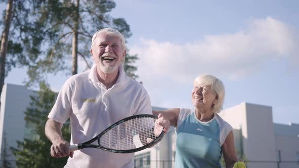 Cover Image for Happy Adult Couple Playing Tennis on a Sunny Day
