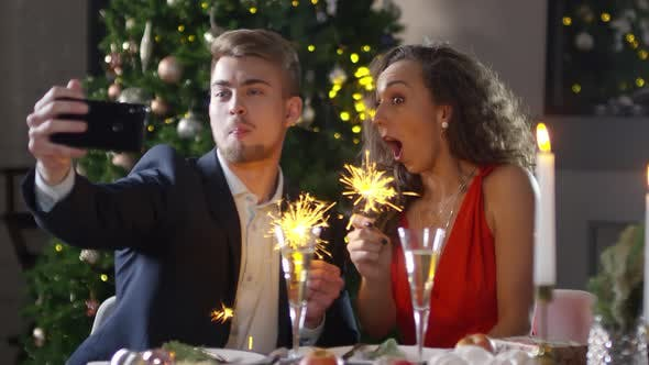 Cover Image for Caucasian Couple Taking Funny Selfies with Burning Sparklers at Christmas