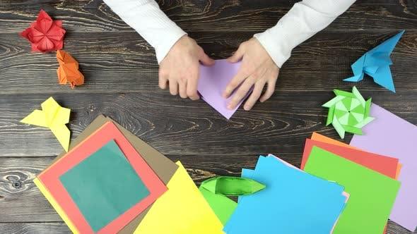 Man Folding Paper To Make Origami.