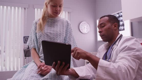 Thumbnail for African doctor talking to woman patient with tablet