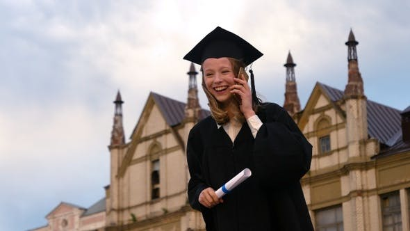 Thumbnail for Graduation: Laughing Girl Dials Phone at Graduation and