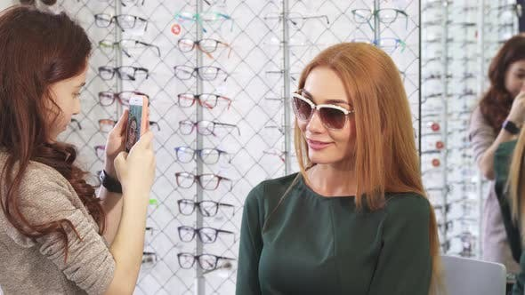 Thumbnail for Little Girl Taking Photos of Her Beautiful Mom Shopping for Sunglasses