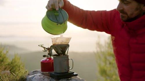 Man Traveller macht Kaffee in Campingausrüstung