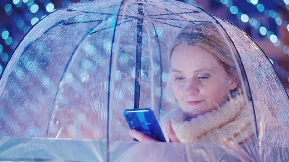 Cover Image for A Woman Is Hiding From the Sleet Under a Transparent Umbrella, Uses a Smartphone