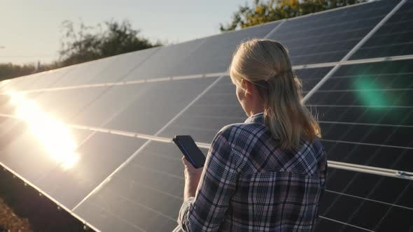 Cover Image for Bakc View of Woman with Smartphone Goes Aquarius Solar Panels at Home Solar Power Plant