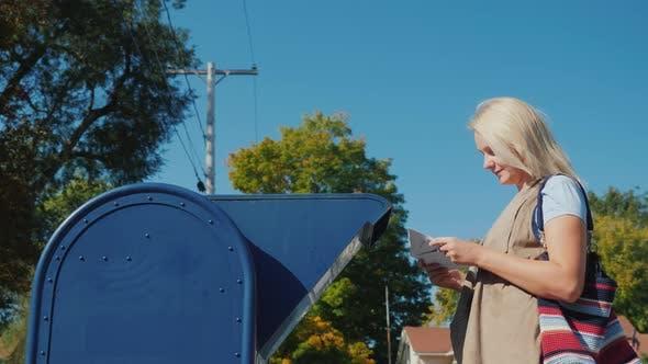 Thumbnail for Eine junge Frau sendet einen Brief in der Post, legt es in den Briefkasten auf der Straße