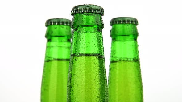 Thumbnail for Three green glass bottles of beer turning over white background