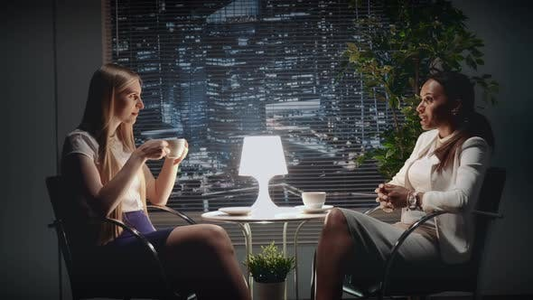 Thumbnail for Two Young Business Women Speaking About Something at the Table with a Cup of Drink