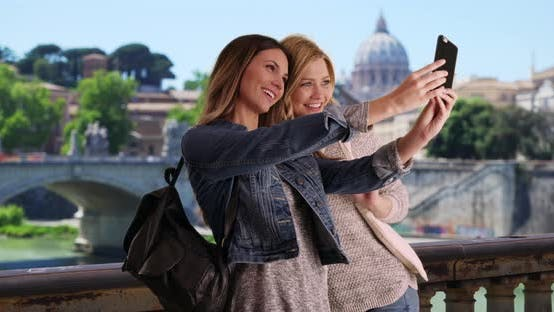 Thumbnail for Couple of female tourists taking selfie with smartphone outside in Rome, Italy