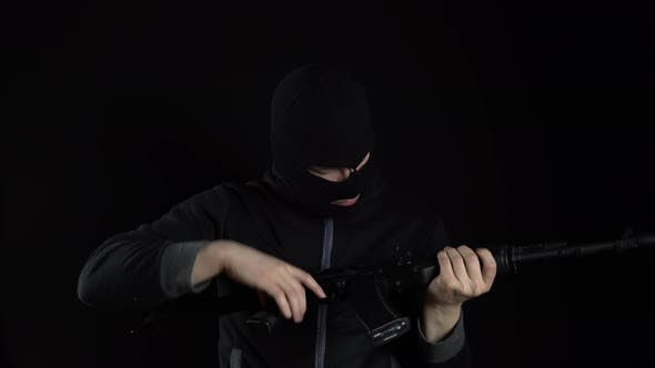 A Man in a Balaclava Mask Stands with an AK-47 Assault Rifle. The Bandit Charges the Machine and