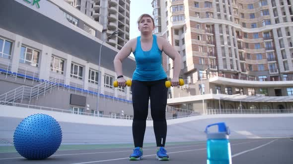 Thumbnail for Overweight Female Training with Dumbbells Outdoors