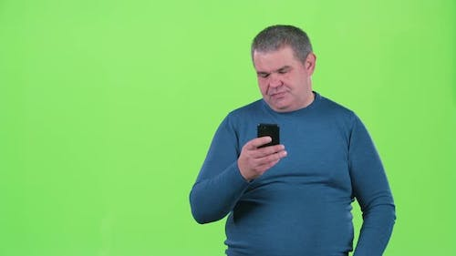 Adult Man Is Looking at the Phone for a Message. Green Screen