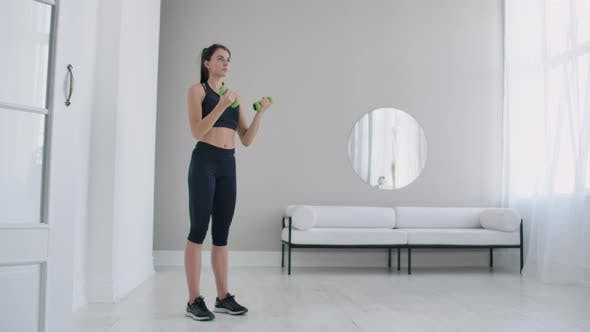 Thumbnail for A Young Caucasian Woman Lifts Dumbbells for Arm and Shoulder Exercises. Lift Dumbbells