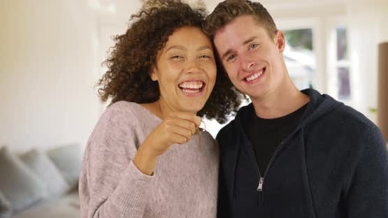 Portrait of happy mixed race multi ethnic millennial couple standing in new apartment with keys. Smi