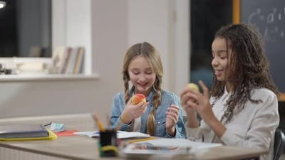 Charming Smiling Caucasian Schoolgirl Sharing Apple with African American Classmate in School