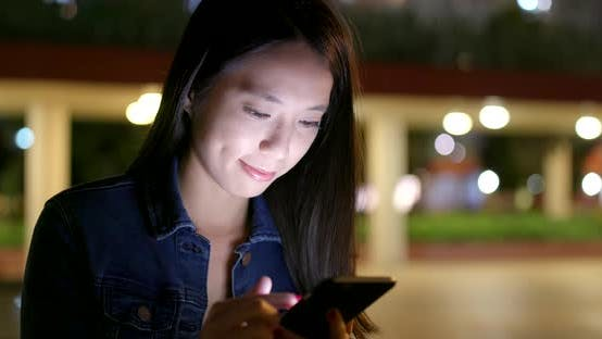 Thumbnail for Woman use of mobile phone on earphone at night