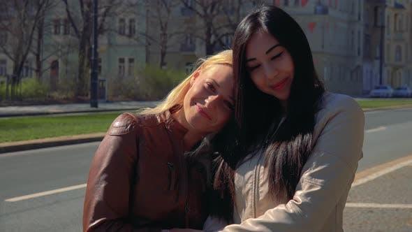 Thumbnail for Ein junger kaukasischer frau und ein junger asiatischer frau umarmen und lächeln bei der kamera in einer straße