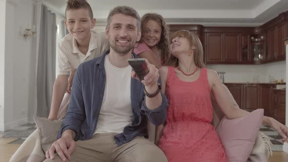 Thumbnail for Portrait Happy Adorable Family Watching TV at Home Together. The Father Holds the Remote and