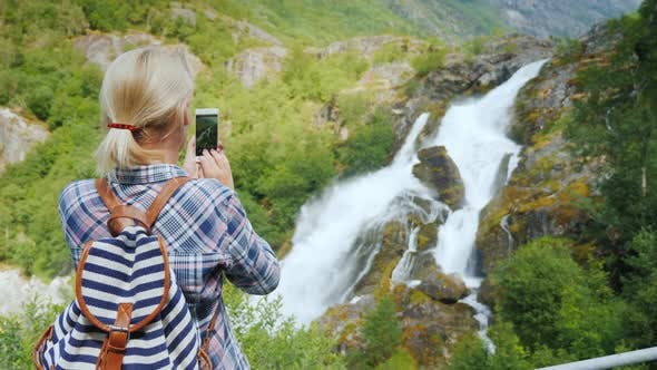 Thumbnail for Woman Takes Pictures of a Picturesque Waterfall in Norway