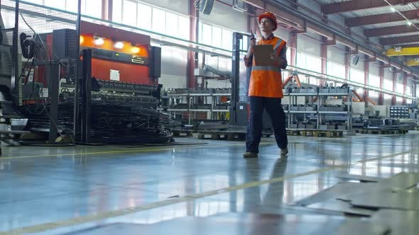 Thumbnail for Female Factory Inspector Walking with Radio Set