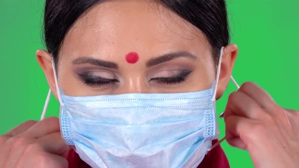 Thumbnail for Portrait of Beautiful Indian Girl Is Looking at the Camera and Takes Off Her Protective Medical Mask