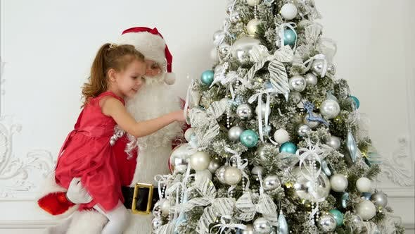 Thumbnail for Santa Claus with Pretty Little Girl Decorating Christmas Tree