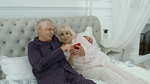 Thumbnail for Senior Elderly Couple Wearing Pyjamas Lying on Bed Looking on Mobile Phone Laughing and Having Fun